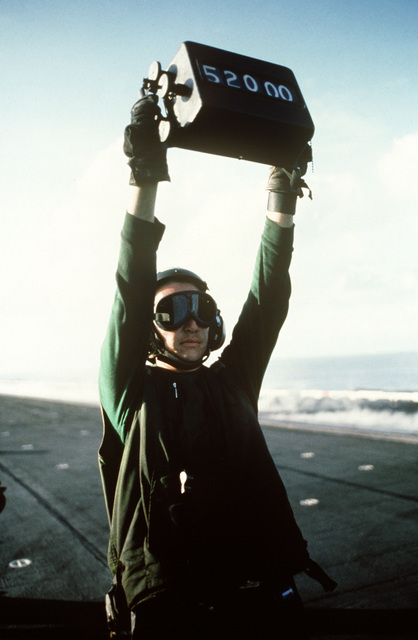 A catapult crewman displays the weight of the aircraft awaiting launch aboard the aircraft carrier USS MIDWAY (CV 41). The proper steam setting, made according to the weight of the aircraft, ensures a successful launch