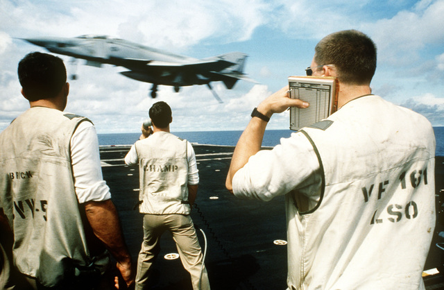 A landing signal officer (LSO), from Fighter Squadron 161 (VF-161), right, protects his ears as an F-4S Phantom II aircraft comes in for a landing aboard the aircraft carrier USS MIDWAY (CV 41). Left side view of the aircraft