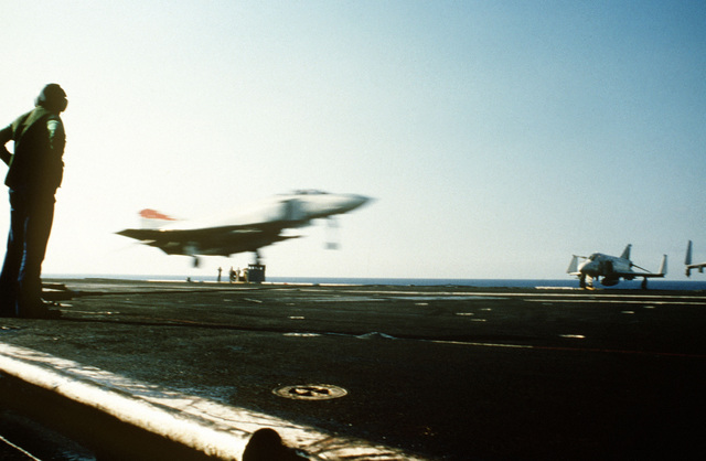 An arresting gear operator watches as an F-4S Phantom II aircraft comes in for a landing aboard the aircraft carrier USS MIDWAY (CV 41). Right front view of the Phantom
