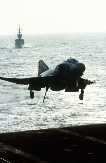 An F-4S Phantom II aircraft, with tail-hook down, prepares to land on the flight deck of the aircraft carrier USS MIDWAY (CV 41)