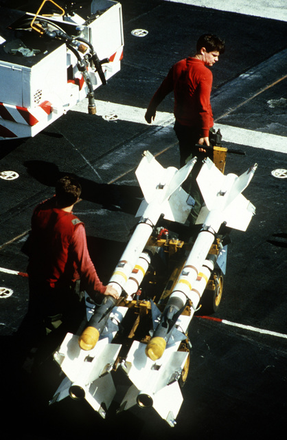 Aviation ordnancemen move four AIM-9 Sidewinder air-to-air missiles across the flight deck of the aircraft carrier USS MIDWAY (CV 41)