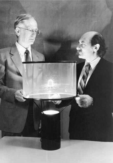 Dr. Wladimiro Calarese (right), aerospace engineer, and Dr. Wilbur Hankey (left), head of the Computational Aerodynamics Group at the Aeronautical Systems Division's Flight Dynamics Laboratory, are pictured with a recently developed 3-D rotating hologram. The illuminated image in the center of the device is an aircraft turret with arrows pointing out the direction of airflow. The 3-D hologram will allow engineers to better study airflow around various aircraft