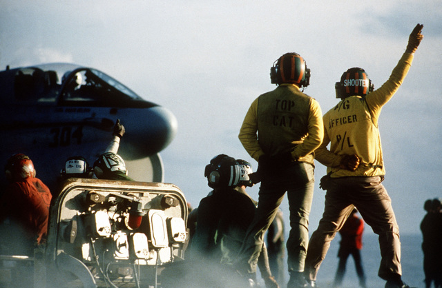 Launching officers aboard the aircraft carrier USS MIDWAY (CV 41) prepare to give the go signal to an A-7E Corsair II aircraft positioned on the catapult