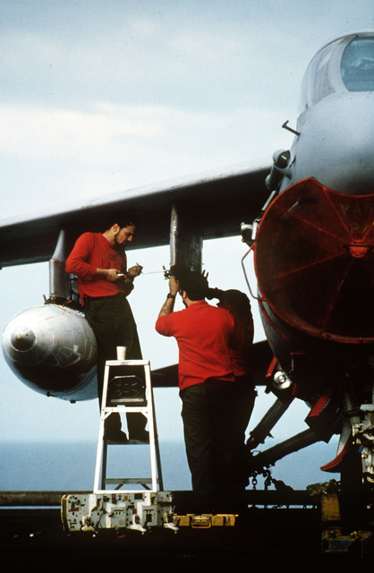 Two aviation ordnancemen install bomb racks on an A-7E Corsair II aircraft parked on the flight deck of the aircraft carrier USS MIDWAY (CV 41)