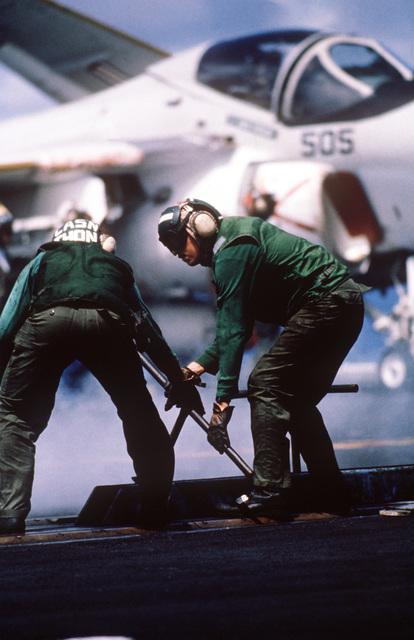 Two catapult crewmen position an A-6 Intruder aircraft shuttle with a tee-bar aboard the aircraft carrier USS MIDWAY (CV 41)