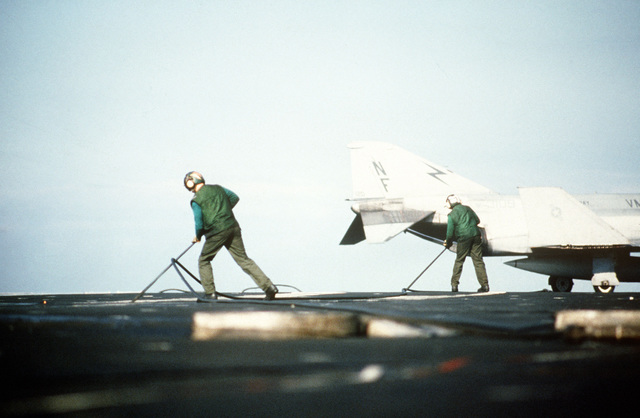 Two green-shirted bar runners guide the arresting cable as it is retracted after an F-4S Phantom II aircraft, background, lands on the flight deck of the aircraft carrier USS MIDWAY (CV 41)