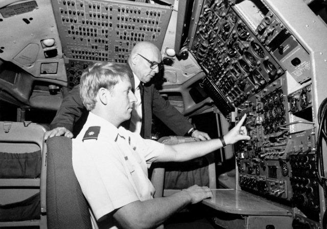 """Major (MAJ) Andrew J. Courtice, seated, and Dick Gieselhart both of the Aeronautical Systems Division (ASD), check out systems aboard the new EC-18B """"in house"""" simulator. The simulator will be used to train pilots from the ASD's 4950th Test Wing to fly worldwide in support of government projects"""