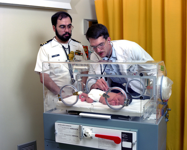 Commander (CDR) (Dr.) Joel C. Labow, left, observes as a third year clinical studies student examines a baby in an incubator during a practice pediatrics course at the Uniformed Services University of the Health Sciences