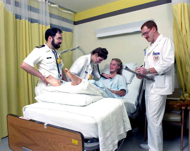 Commander (CDR) (Dr.) Joel C. Labow looks on as third year students participate in patient assessment during clinical studies at the Uniformed Services University of the Health Sciences