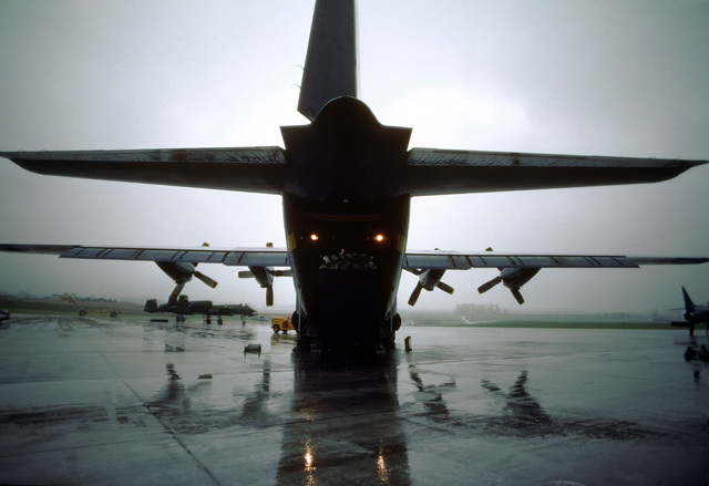 """A rear view of the Blue Angels Flight Demonstration Squadron 130 Hercules aircraft, unofficially known as """"Fat Albert,"""" parked on the flight line. Operated by a Marine Corps crew, the C-130 transports personnel, fuel, and supplies to Blue Angels performances"""