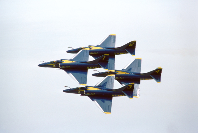 Four Blue Angels Flight Demonstration Squadron A-4F Skyhawk II aircraft execute a banked turn while in a diamond formation during an air show