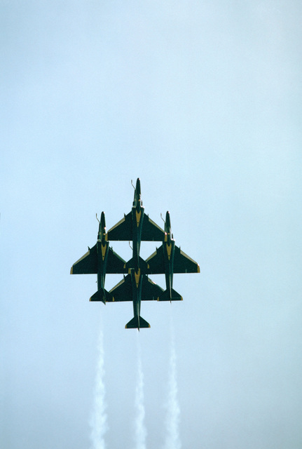Four Blue Angels Flight Demonstration Squadron A-4F Skyhawk II aircraft in a diamond formation during an air show