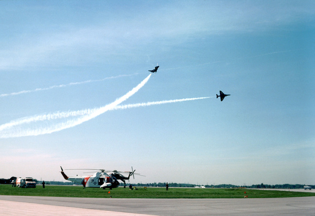 Two Blue Angels Flight Demonstration Squadron A-4F Skyhawk II aircraft execute a low-level maneuver during an air show. Parked on the flight line are a Coast Guard HH-52A Sea Guard helicopter and a CH-54 Tarhe helicopter
