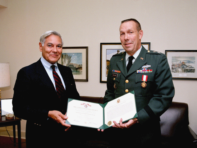 Nestor D. Sanchez, deputy assistant secretary of defense for inter-American affairs, presents the Distinguished Service Medal to Major General (MGEN) Neil Creighton upon his retirement from the US Army. Creighton served as director, Inter-American Region, Office of the Assistant Secretary of Defense for International Security Affairs, prior to his retirement