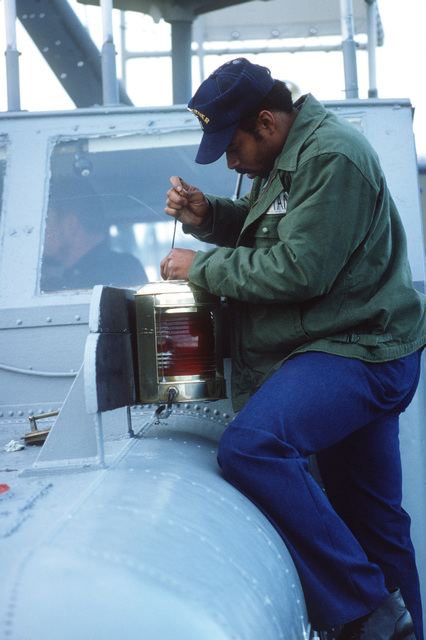 A crewman performs maintenance on the red side light on the drone recovery craft USS RETRIEVER (DR 1) moored at Pier No. 5