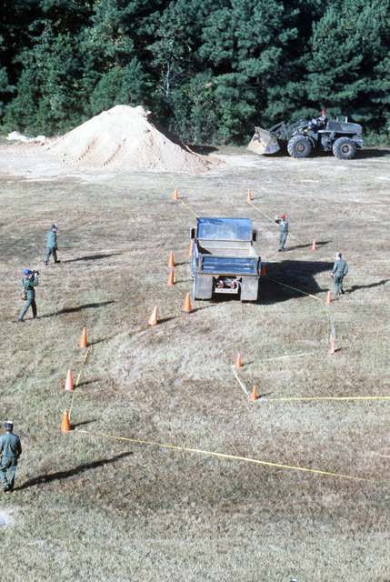 A dump truck proceeds through the equipment operation course during a Prime Beef competition. A Case M14 loader is visible in the background