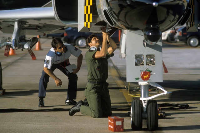 A judge observes a weapons technician as he works on a 191st Fighter Interceptor Group, Michigan Air National Guard, F-4C Phantom II aircraft during weapons loading competition for the air-to-air weapons meet WILLIAM TELL '84