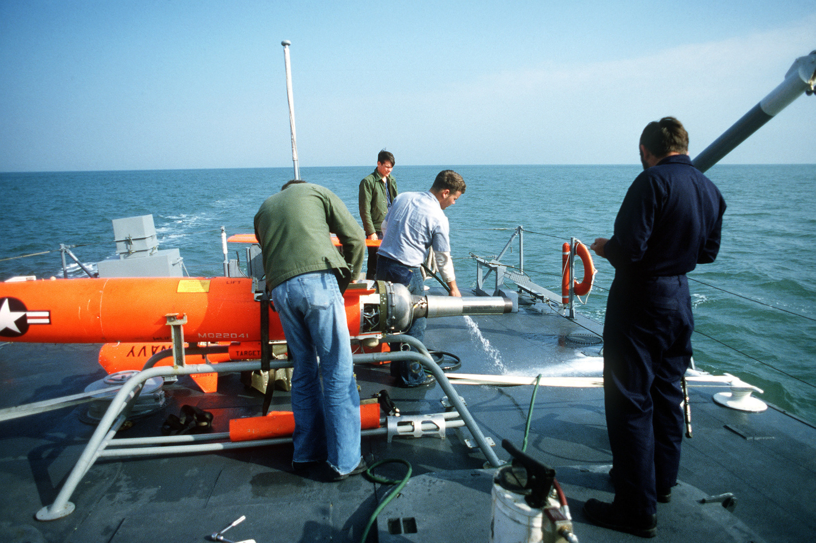 Crewman prepare two Northrop NV-105 Chukar II (MQM-74) lightweight target drones for launching from the drone recovery craft USS RETRIEVER (DR 1)