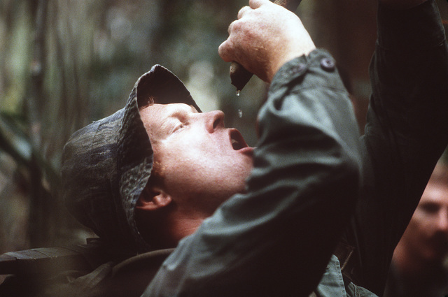 STAFF Sergeant (SSGT) William Sine drinks from a water vine during a survival training exercise conducted by the US Navy Jungle Survival School