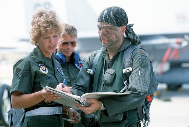 STAFF SGT. Kimberly Davis helps a pilot fill out a log book during the air-to-air weapons meet William Tell '84