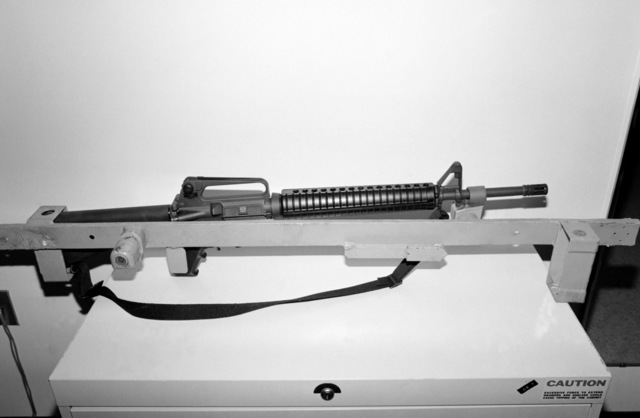 A locking storage rack aboard the amphibious assault ship USS SAIPAN (LHA 2) that has been modified to accept the M249 squad automatic weapon (SAW) (shown in rack) and the M16A2 rifle