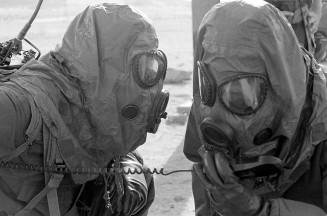 Members of Battery N, 5th Battalion, 11th Marines, try to establish radio communications during a 27th Marine Regiment nuclear, biological and chemical exercise held at the Marine Corps Air Ground Combat Center. They are wearing M-17A1 protective masks