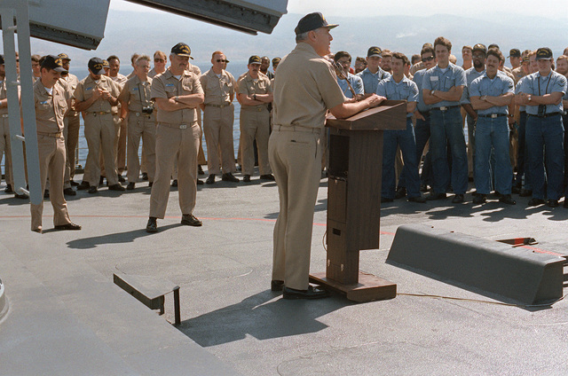 Captain (CAPT) Joseph F. King, left, commanding officer of the nuclear-powered guided missile cruiser USS VIRGINIA (CGN 38), and his crew, listen as Admiral (ADM) James D. Watkins, chief of naval operations, addresses them during a visit. The ship is providing support for Marines stationed in Beirut, Lebanon