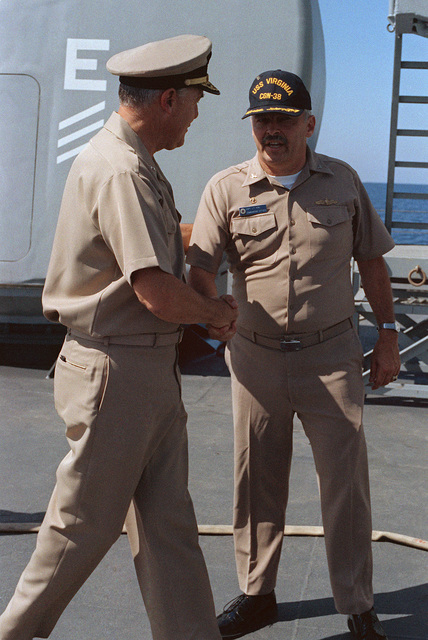 Captain (CAPT) Joseph F. King, right, commanding officer of the nuclear-powered guided missile cruiser USS VIRGINIA (CGN 38), welcomes Admiral (ADM) James D. Watkins, chief of naval operations, aboard the ship. The ship is providing support for Marines stationed in Beirut, Lebanon