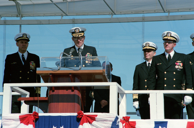 On the speakers platform are, right to left: Captain M. Farmer, Commanding Officer, gold; Admiral K.R. Mckee Deputy Commander for Nuclear Propulsion, Naval Sea Systems Command; Captain R.L. Tindal, Commanding Officer, blue, (speaking) and Vice Admiral N. Thunman, Deputy CHIEF and Naval Operations, Submarine Warfare, during the commissioning of the USS HENERY M. JACKSON (SSBN 730)