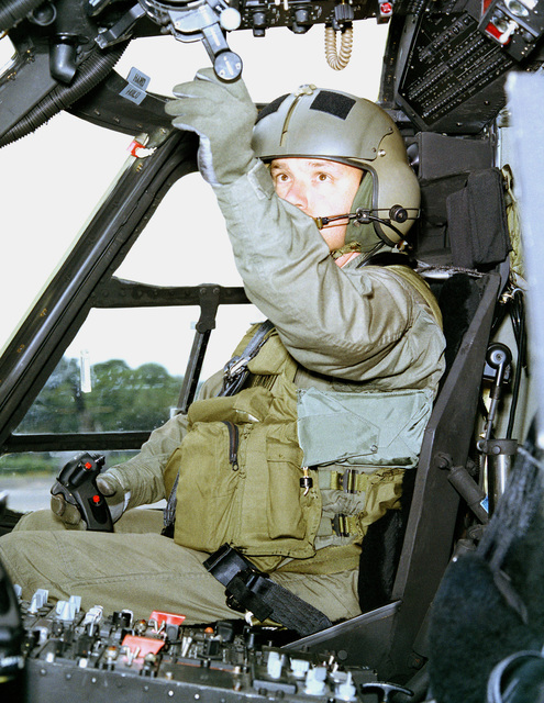 First Lieutenant David J. Cole, 210th Combat Aviation Battalion, 193rd Infantry Brigade, Panama, wears the aircrew survival armor recovery vest, inserts and packets (SARVIP) while performing pre-operational checks in a UH-60 Black Hawk helicopter. The Army is conducting the wear/storage testing of SARVIP in a tropical environment at the US Army Tropic Test Center