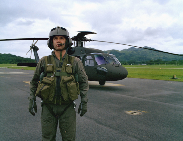 The proper wear of the aircrew survival armor recovery vest, inserts and packets (SARVIP) with flight gear is demonstrated by First Lieutenant David J. Cole, 210th Combat Aviation Battalion, 193rd Infantry Brigade, Panama. A UH-60 Black Hawk helicopter is in the background. The SARVIP is presently undergoing Development Test II at the US Army Tropic Test Center