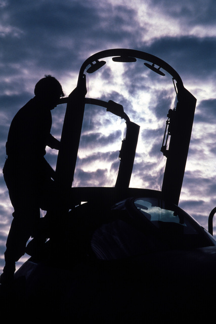 A silhouetted view of an Air National Guardsman as he performs pre-flight maintenance on an RF-4C Phantom Ii aircraft during Exercise PHOTO FINISH '81