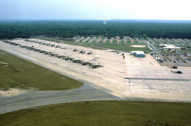 An aerial view of Air National Guard RF-4C Phantom II aircraft on the flight line during Exercise PHOTO FINISH '81. Also visible is an RF-8G Crusader photo reconnaissance aircraft, back row, fourth from right, and two UH-1 Iroquois helicopters, right