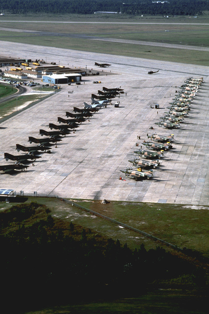 An aerial view of Air National Guard RF-4C Phantom II aircraft on the flight line during Exercise PHOTO FINISH '81. The two gray aircraft on the left are Navy RF-8G Crusader photo reconnaissance aircraft, and visible in the background is a UH-1 Iroquois helicopter
