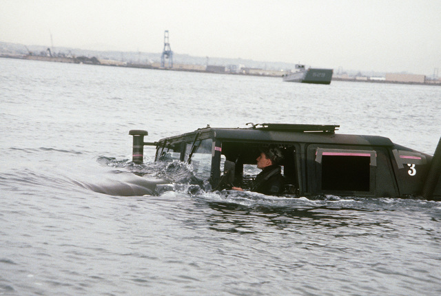 An M998 High-Mobility Multipurpose Wheeled Vehicle is tested by Corporal (CPL) Peter Proietto, 1ST Marine Division, for its ability to ford up to 56 inches of water. The M998 will replace several lightweight vehicles used by the US military