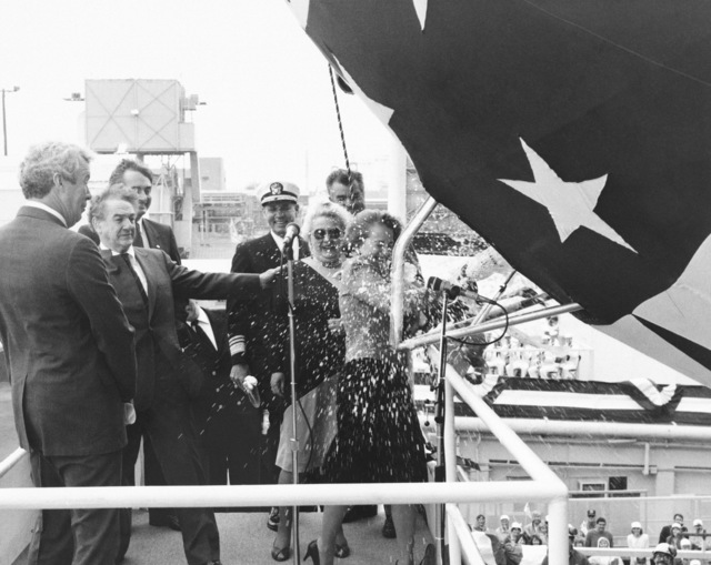 Vicki Paisley, ships sponsor, breaks a bottle of champagne across the bow of the Los Angeles class nuclear-powered attack submarine USS CHICAGO (SSN 721) at the conclusion of the launch ceremony. Vice Admiral Nils Thunman, Deputy CHIEF of Naval Operations, Submarine Warfare, stands in the background center