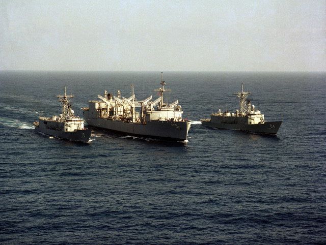 A starboard bow view of the replenishment oiler USS WABASH (AOR 5) (center) conducting an underway replenishment of the guided missile frigate USS DUNCAN (FFG 10). The Australian frigate HMAS DARWIN (F-04) is underway on the right