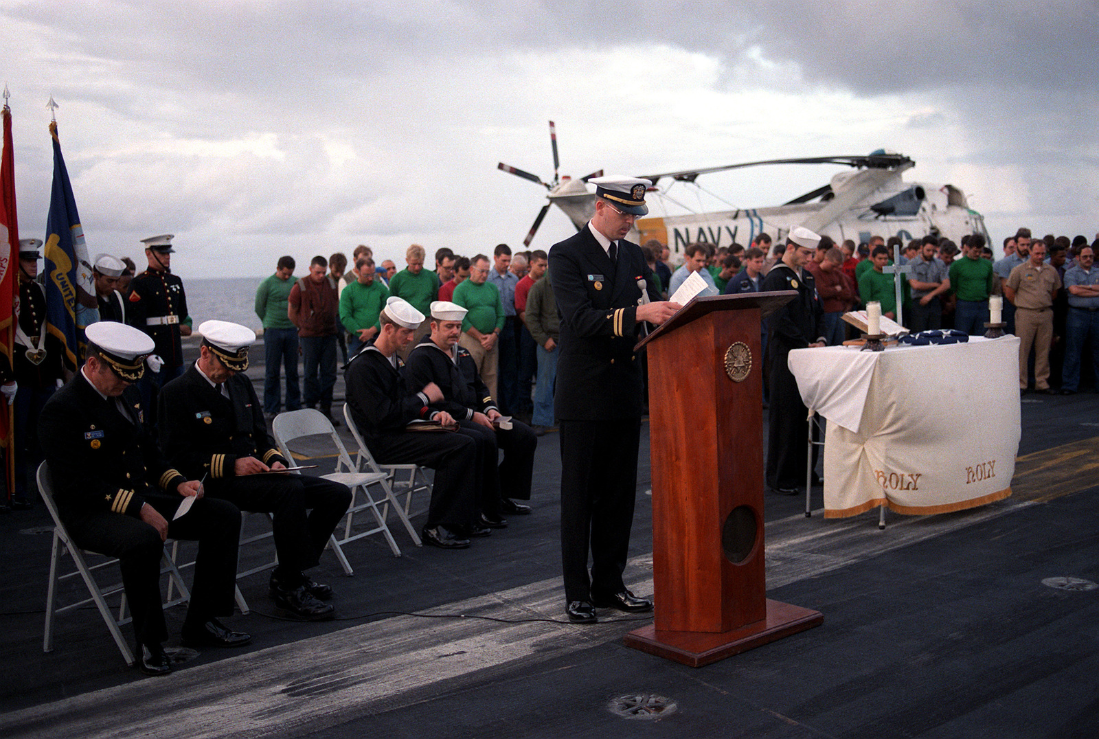 Chaplain (LT.) Paul F. Soderquist leads the crew of the nuclear-powered aircraft carrier USS DWIGHT D. EISENHOWER (CVN-69) in the invocation during a memorial service for Aviation Machinist's Mate 3rd Class Charles D. Elliot. Elliot was lost at sea in heavy weather while serving aboard the Eisenhower