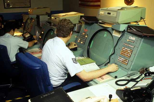 Air Force personnel monitor graphic display terminals at the Missile Warning Agency inside the North American Air Defense (NORAD) Space Command Cheyenne Mountain Complex