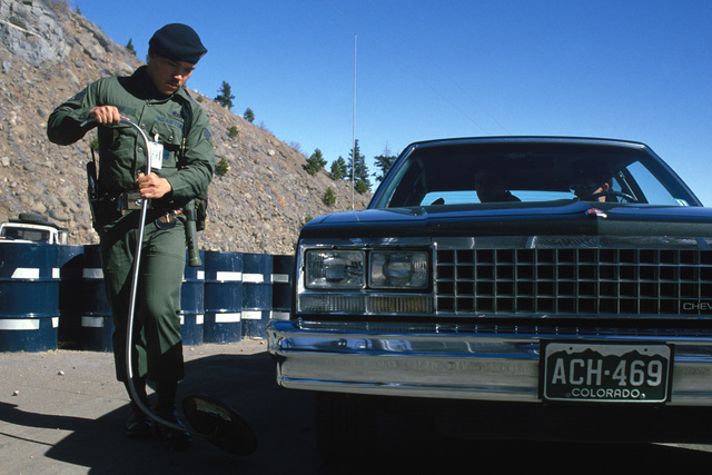 An Air Force security policeman uses a mirror to check underneath a vehicle at the entrance to the North American Air Defense (NORAD) Space Command Cheyenne Mountain Complex