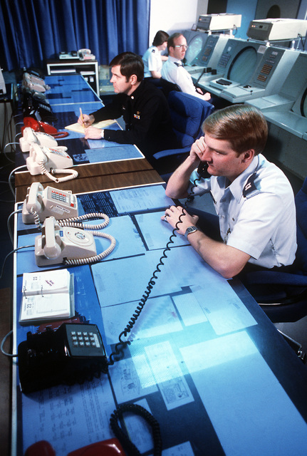 CAPT. Rick Chase, space intelligence officer, and Navy LT. CMDR. Gary Van Horn man the phones in the Space Defense Operations Center at the North American Air Defense (NORAD) Space Command Cheyenne Mountain Complex