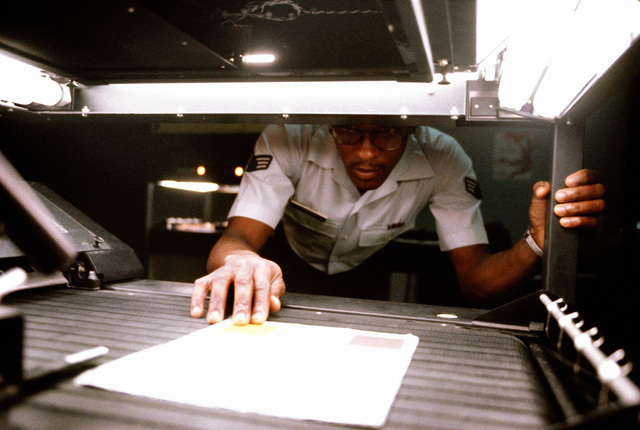 SENIOR AIRMAN Reginald Parker copies personnel records on the office camera at the Micrographics Systems Branch of the Air Force Manpower and Personnel Center. The Micrographics Systems Branch uses a microfiche system to maintain the personnel records of all active-duty officers and enlisted members of the Air Force