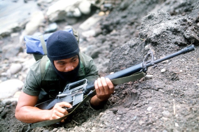 A member of the Philippine Special Forces, armed with an M16A1 rifle, prepare for battle as part of the reenactment of General MacArthur's landing at Red Beach on October 20, 1944