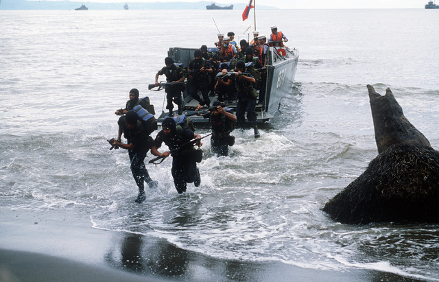 Members of the Philippine Special Forces come ashore from a mechanized landing craft (LCM 8) as part of the reenactment of General MacArthur's landing at Red Beach on October 20, 1944