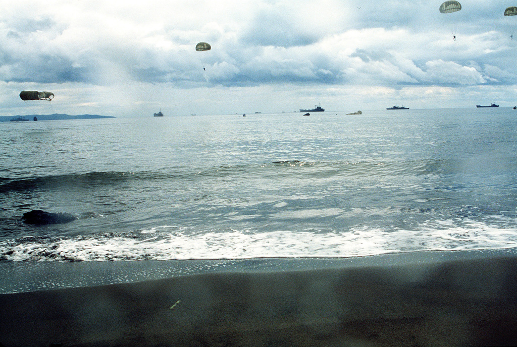 Navy sea-air-land (SEAL) team members parachute from helicopters during a reenactment of General MacArthur's landing at Red Beach on October 20, 1944