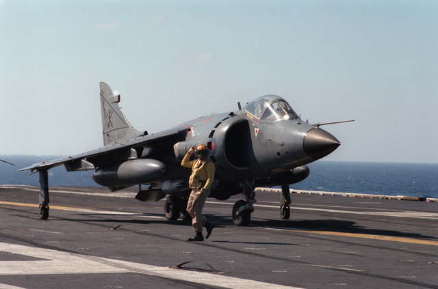 A plane director signals instructions while standing in front of a British Royal Navy FRS.Mk 1 Sea Harrier aircraft aboard the nuclear-powered aircraft carrier USS DWIGHT D. EISENHOWER (CVN 69)