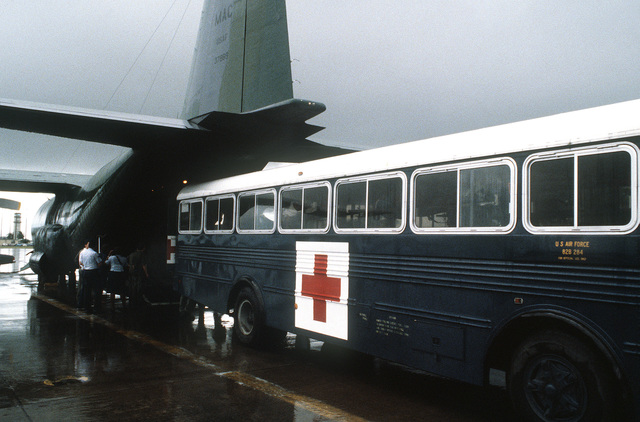 A hospital bus backs up to a C-130 Hercules aircraft to transport victims of the Pines Hotel fire to the Regional Medical Center. Over 200 World War II veterans and their families were staying at the hotel in Baguio while attending a reunion commemorating the 40th anniversary of the liberation of the Philippines