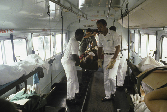 A stretcher team carries a victim of the Pines Hotel fire onto a bus for transport to the Regional Medical Center. Over 200 World War II veterans and their families were staying at the hotel in Baguio while attending a reunion commemorating the 40th anniversary of the liberation of the Philippines