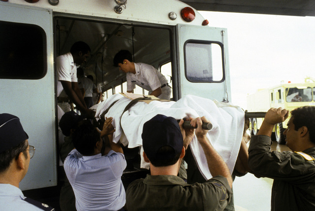 A stretcher team lifts a victim of the Pines Hotel fire onto a bus for transport to the Regional Medical Center. Over 200 World War II veterans and their families were staying at the hotel in Baguio while attending a reunion commemorating the 40th anniversary of the liberation of the Philippines