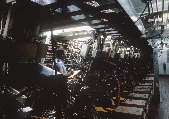 A US Air Force quality assurance evaluator inpsects electrical equipment in the subarray face of the Cobra Dane radar system operated by the 16th Surveillance Squadron